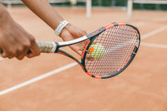 Close-up of male hand holding tennis ball and racket Stock Photo
