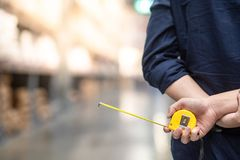 Male hand holding tape measure in warehouse. Close up of male hand holding yellow tape measure in warehouse. Furniture product design measuring concept stock photos