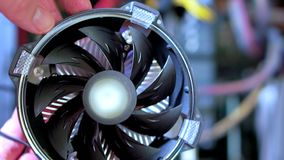 Close-up of male hand installing new CPU fan. He`s inspecting the fan.