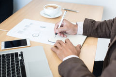 Close-up of male hand making notes in office.  Royalty Free Stock Image