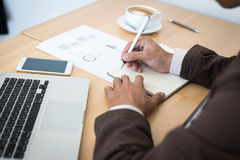 Close-up of male hand making notes in office.  Stock Photos