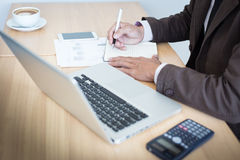 Close-up of male hand making notes in office.  Stock Image