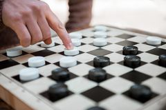 Arm of man pushing chequer on board. Close up of male hand moving white checker forward on chessboard royalty free stock photo