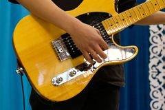 Close-up of the male hand of a musician playing on a yellow electric guitar. royalty free stock images