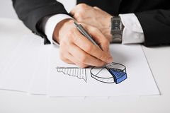 Close up of male hand with pen drawing graph. Business, marketing, planning and people concept - close up of male hand with pen drawing graph on white paper Stock Photography