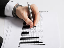 Close up of male hand with pen drawing graph Stock Photos