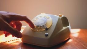 Close up of male hand picking up the receiver of a vintage retro rotary telephone and answering the phone. Close up of male hand picking up the receiver of a stock footage