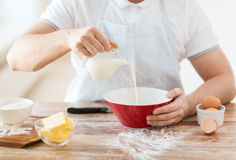 Close up of male hand pouring milk in bowl Stock Photography