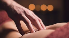 Close-up male hand of a professional physiotherapist masseur doing lumbar massage to a female patient in a massage