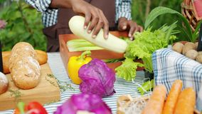 Close-up of male hand putting organic vegetables on table in farm market. Waiting for customers selling healthy food. Business, nutrition and people concept stock video footage