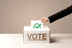Close up of male hand putting vote into a ballot box. On grunge background Royalty Free Stock Image