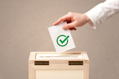 Close up of male hand putting vote into a ballot box Royalty Free Stock Images