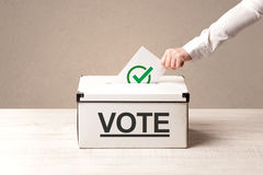 Close up of male hand putting vote into a ballot box Royalty Free Stock Image