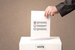 Close up of male hand putting vote into a ballot box Royalty Free Stock Photography