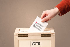 Close up of male hand putting vote into a ballot box Royalty Free Stock Photos