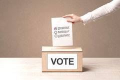 Close up of male hand putting vote into a ballot box Stock Photography