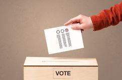 Male hand putting vote into a ballot box, on grungy background Royalty Free Stock Photos