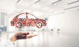 Close up of male hand showing car symbol made with gears and cog Royalty Free Stock Photo