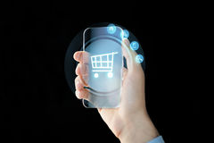 Close up of male hand with transparent smartphone. Business, future technology and people concept - close up of male hand holding and showing transparent Royalty Free Stock Images