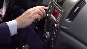 Close-up of male hand turning on radio on car. Close-up of male hand turning on radio on control panel system in car stock footage