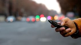 Close-up of male hand using cell phone near highway. Bokeh of car headlights.  stock footage