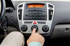 Close up of male hand using climate control in car Royalty Free Stock Image