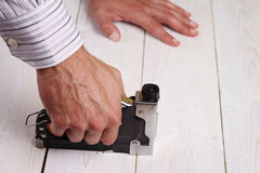 Close up on male hand using electric nail hammer machine. Man Doing DIY at home Stock Photos