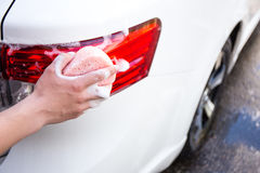 Close up of male hand washing rear lights of car by sponge. Close up of male hand washing rear lights of white car by sponge Stock Images