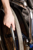 Close-up of male hand on wheel of wheelchair Royalty Free Stock Images
