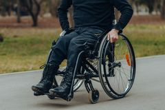 Close-up of male hand on wheel of wheelchair during walk in park stock photo