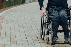 Close-up of male hand on wheel of wheelchair during walk in park royalty free stock photo