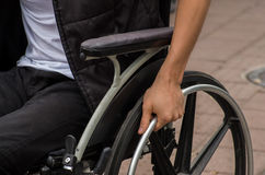 Close-up of male hand on wheel of wheelchair during walk in park Stock Images