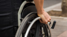 Close-up of male hand on wheel of wheelchair during walk in park Stock Photography