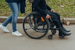 Close-up of a male hand on a wheel of a wheelchair during a walk in the park. Walk together in the park royalty free stock images