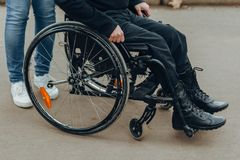 Close-up of a male hand on a wheel of a wheelchair during a walk in the park. Walk together in the park royalty free stock photo