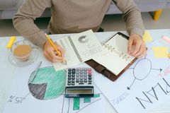 Close up male hand writing make note with calculate about cost a. T home office Stock Photography