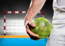 Close-up of male handball player holding ball against goal post. Digital composition of male handball player holding ball against goal post Royalty Free Stock Photos