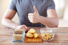 Close up of male hands with carbohydrate food. Healthy eating, diet, gesture and people concept - close up of male hands showing thumbs up with carbohydrate food royalty free stock images