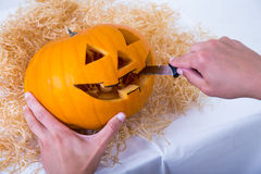Close up of male hands carving pumpkin Jack-O-Lantern for Hallow Stock Photos