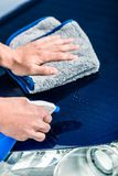 Hands cleaning car with spray cleaner and microfiber towel. Close-up of male hands cleaning car with spray cleaner and microfiber towel outdoors at car wash Stock Photos