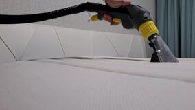 Close-up of male hands cleaning the mattress professional extraction method