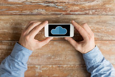 Close up of male hands with cloud on smartphone. Business, education, people and technology concept - close up of male hands holding smartphone with cloud Royalty Free Stock Photo