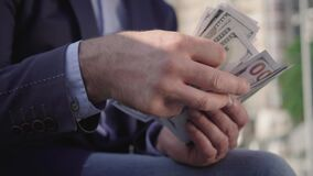 Close-up of male hands counting dollar banknotes outdoors on sunny day. Unrecognizable wealthy man holding pack of cash
