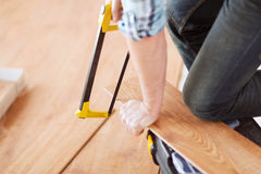 Close up of male hands cutting parquet floor board Royalty Free Stock Photos