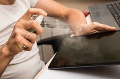 Close up. Male hands disinfect the tablet display with alcohol disinfectant. The sanitizer is sprayed across the screen