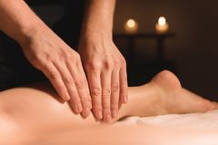 Close-up of male hands doing calf massage of female legs in a dark room with candles in the background. Cosmetology and royalty free stock photo