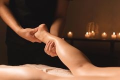 Close-up of male hands doing calf massage of female legs in a dark room with candles in the background. Cosmetology and. Spa treatments stock photography