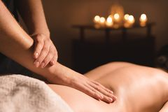 Close-up male hands doing healing massage with oil to a young girl in a dark cosmetology office. Dark key royalty free stock photo