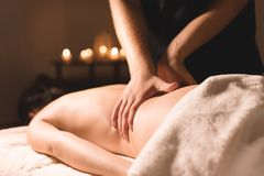 Close-up male hands doing healing massage with oil to a young girl in a dark cosmetology office. Dark key stock photo