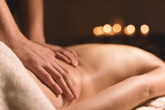 Close-up male hands doing healing massage with oil to a young girl in a dark cosmetology office. Dark key.  stock photos